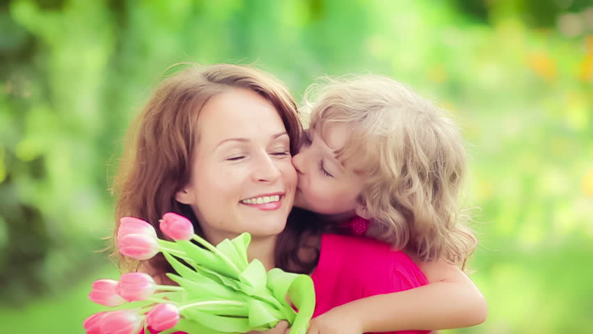Child giving flowers to the young woman in spring park. Mothers day holiday concept. Slow motion