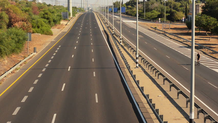 Rishon LeZion, Israel-October 4,2014: Two cyclists riding on deserted highway early morning. Once a year, on Yom Kippur (Jewish Day of Atonement) the country goes quiet as almost all cars stop running