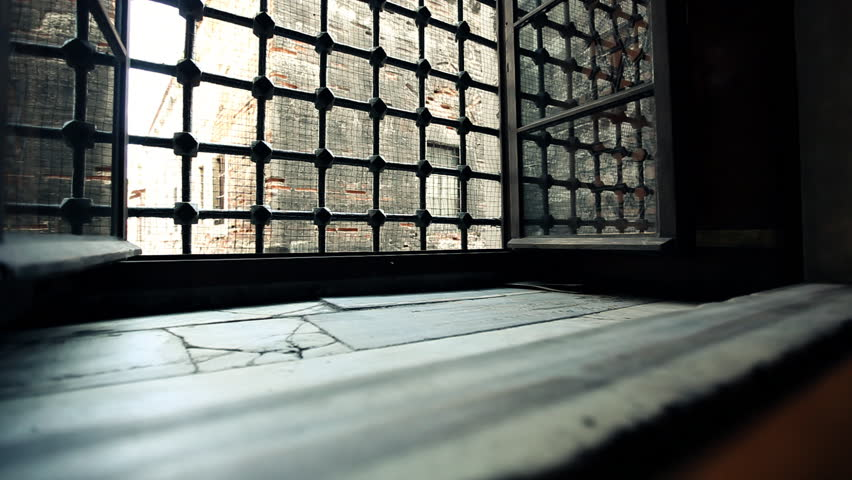 Light object passing open ancient window with iron grid and leaving trail of