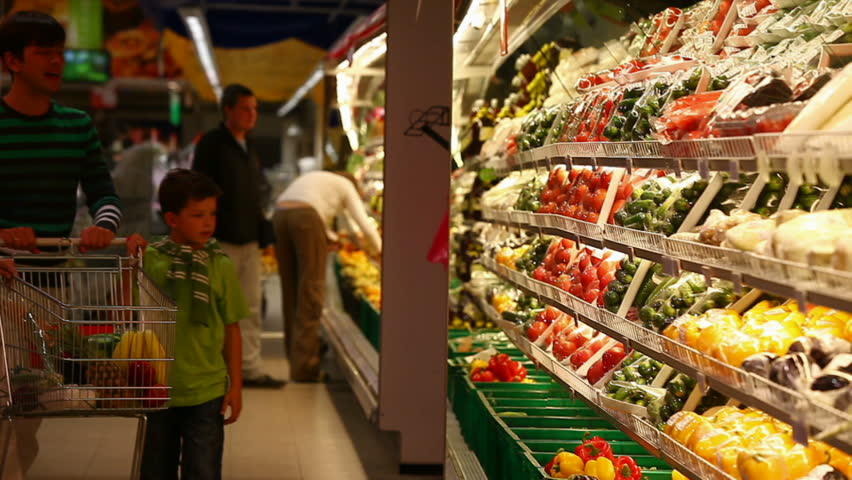 A family of four approaching vegetable row in the supermarket, taking some vegetables and placing them into the trolley | Shutterstock HD Video #882874