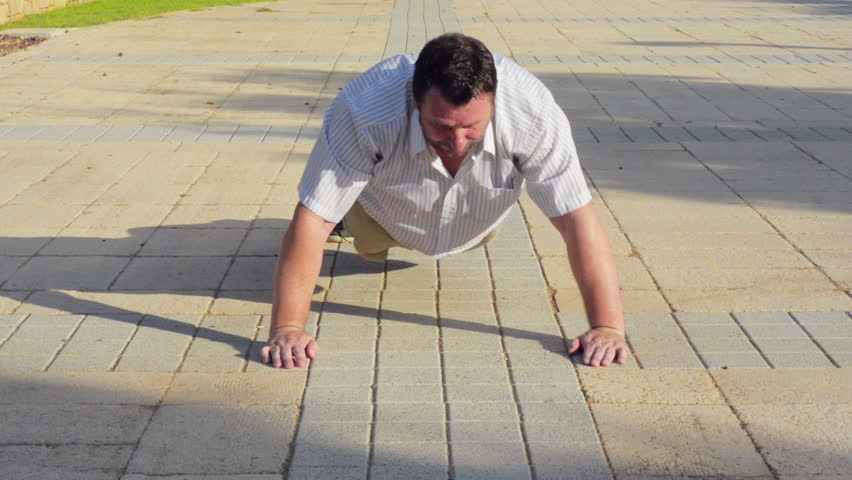 50 year old fat man tries to do push-ups on a pavement stone in summer day. But his efforts are unsuccessful
