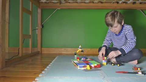 Tracking dolly shot of young boy playing with Lego on floor in his room