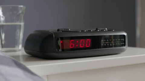 Tracking into digital alarm clock, alarm ringing 6am