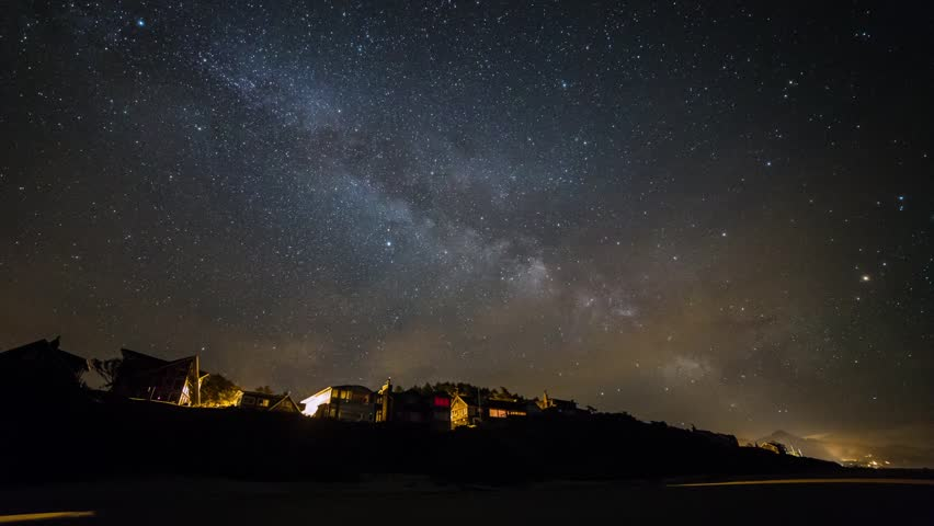 Time lapse of milky way above houses by the beach. Taken at Cannon Beach, Oregon