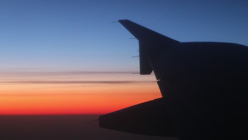 Airplane flying in the sky with the sunset in the background. Silhouette of the airplane wing from the window.