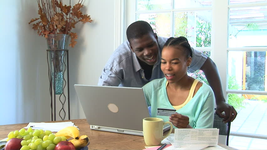 Young African American couple using credit card and laptop