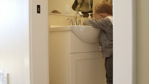 A toddler washes his hands in the bathroom sink after using the bathroom