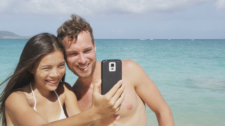 Young happy couple taking selfie (self portrait) on beach using smartphone mobile cell phone camera. Young happy Asian woman and Caucasian man. RED EPIC SLOW MOTION 96 FPS. | Shutterstock HD Video #8947975