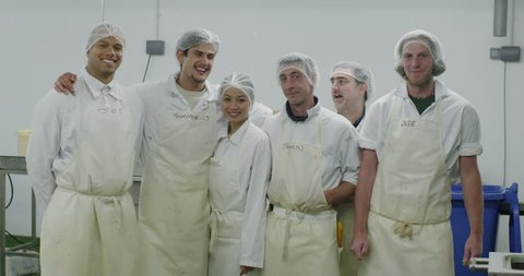 4K Portrait of cheerful team of workers in a seafood processing factory