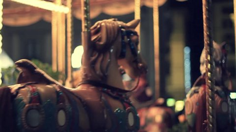 FLORENCE, ITALY - SEPTEMBER 25, 2014: Merry-go-round carousel at night with adults and children riding ponies.