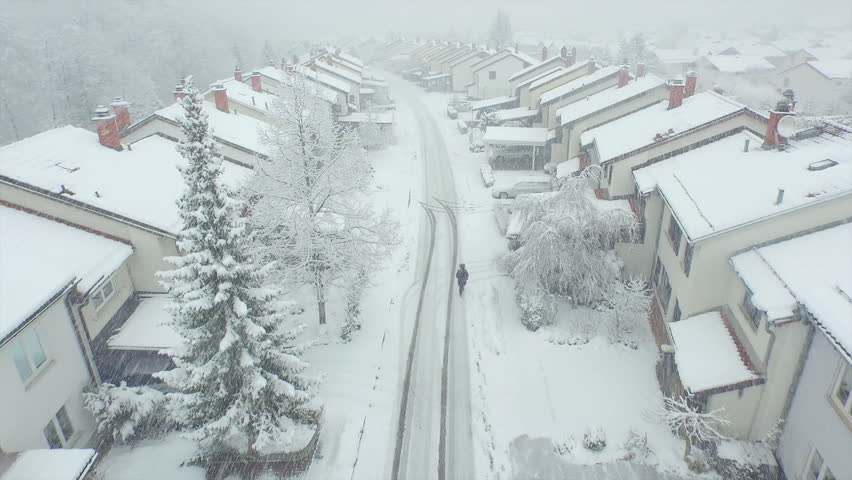 AERIAL: Lonely person walking through suburban town in snowstorm