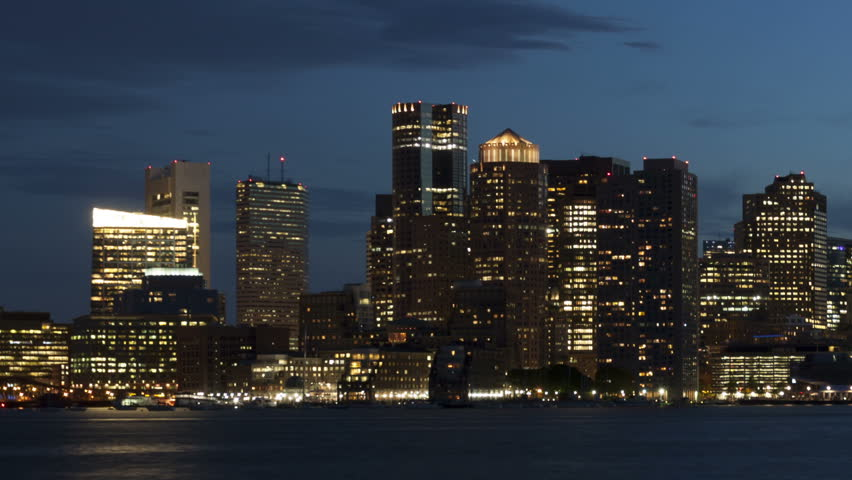 Time lapse close up with a slow pan shot of Boston city skyline with clouds passing by at twilight with reflection of the skyscrapers over Charles River