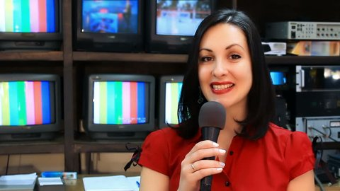 TV reporter in front of the studio camera ; Beautiful newscaster presenting news in TV studio,video clip
