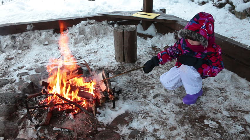 Child in winter clothes sitting with stick near bonfire in a wooden canopy. - HD & Putting Steel Saucepans Into Open Fire Outdoors To Warm Water For ...