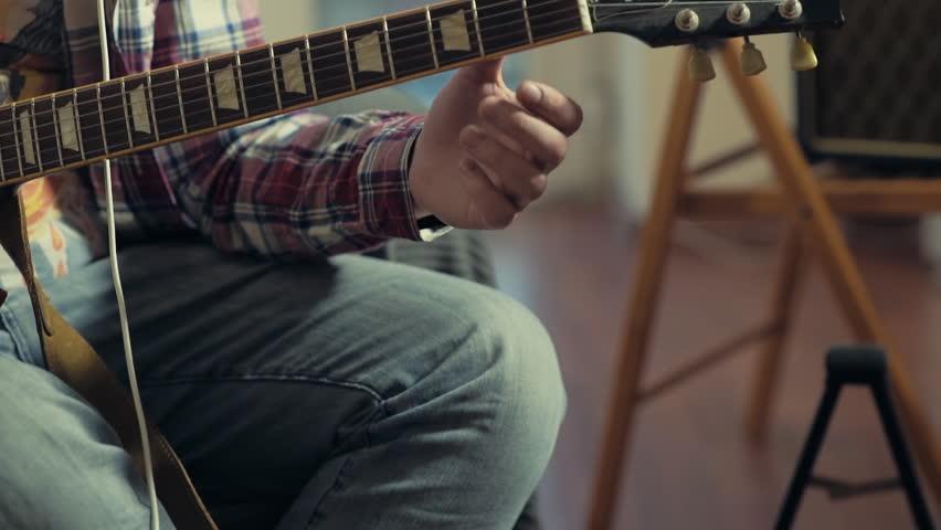 man tuning electric guitar slow motion #9059782