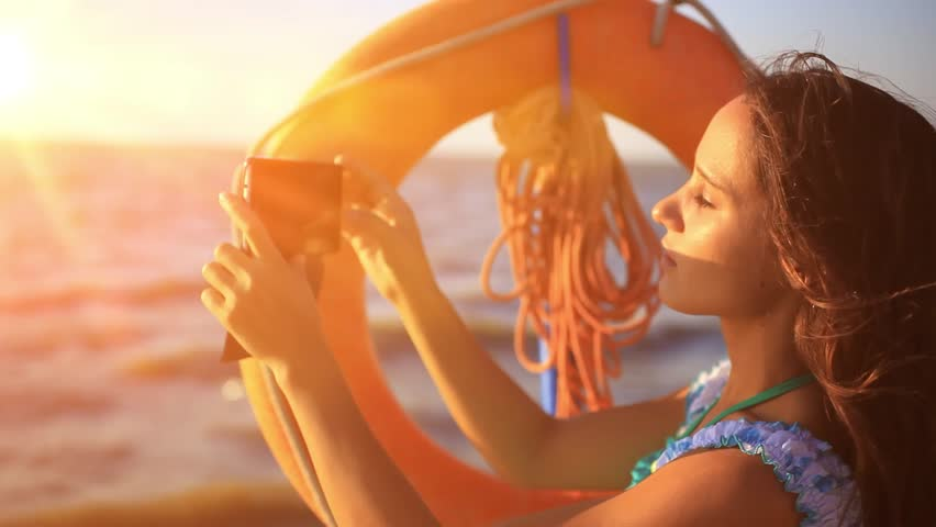 Young beautiful woman taking pictures with smartphone at sunset. Selfie against amazing seascape near lifebelt. HD. 1920x1080   Shutterstock HD Video #9073172