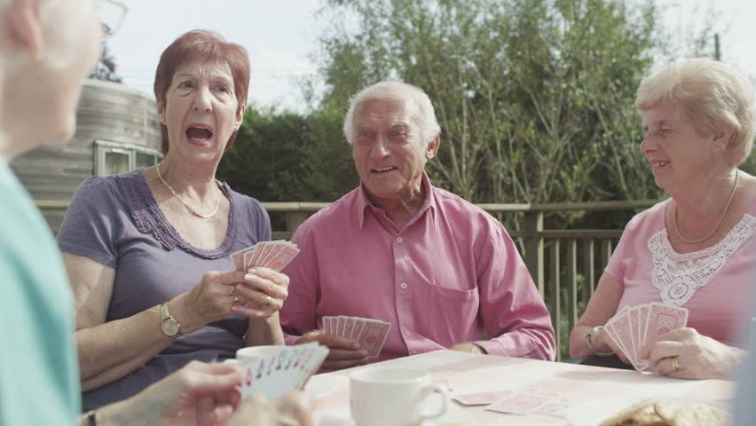 4K Happy group of senior friends playing cards in the garden with cups of tea -