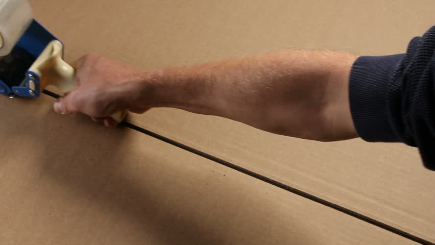 A hand pulls a tape gun across a corrugated cardboard box to tape up a seam.