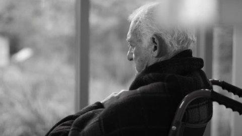 4K Black & white portrait of lonely senior man sitting by the window