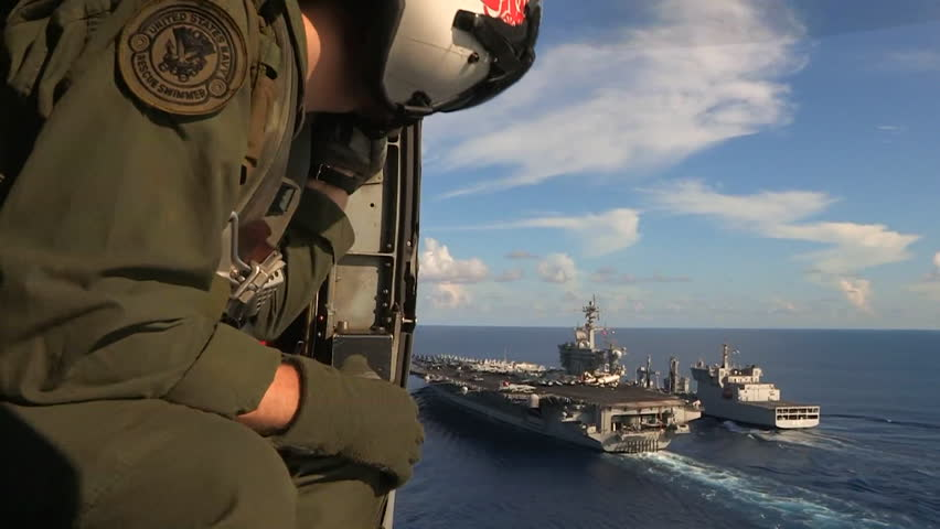 CIRCA 2010s - Aerial from a helicopter with military personnel visible over an aircraft carrier as sea.