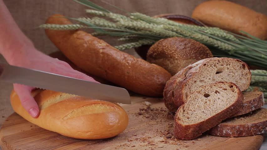 Cutting white bread of  bread knife on a wooden board   Shutterstock HD Video #9186302
