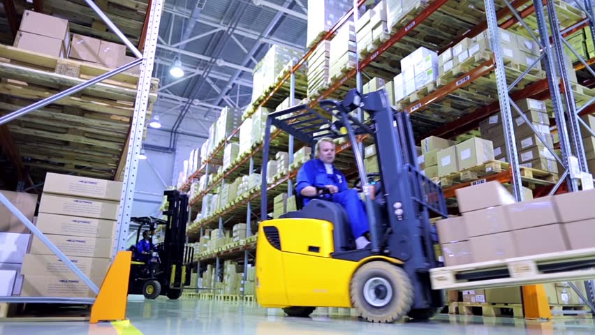 Forklift trucks move between large metal shelves at a modern warehouse and unload pallets with cardboard boxes | Shutterstock HD Video #9190772
