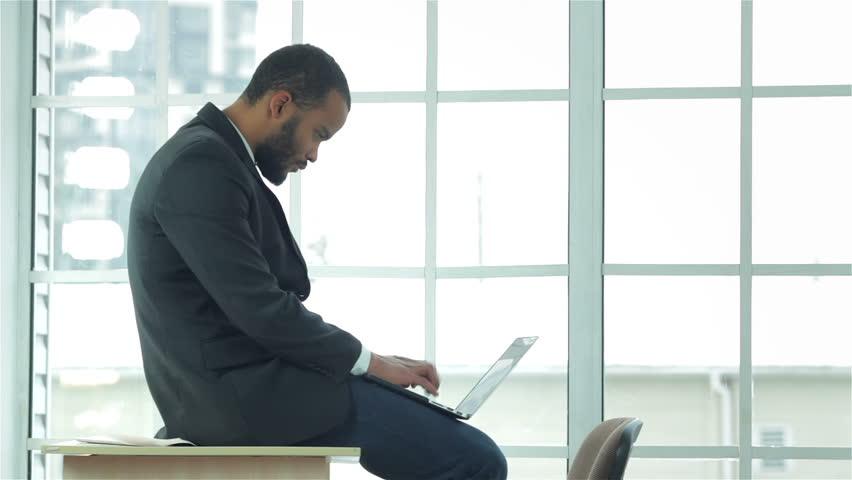 African businessman sitting at desk works on laptop. Confident businessman sitting at desk in office while holding laptop in hand. Businessman dressed in formal wear | Shutterstock HD Video #9190832