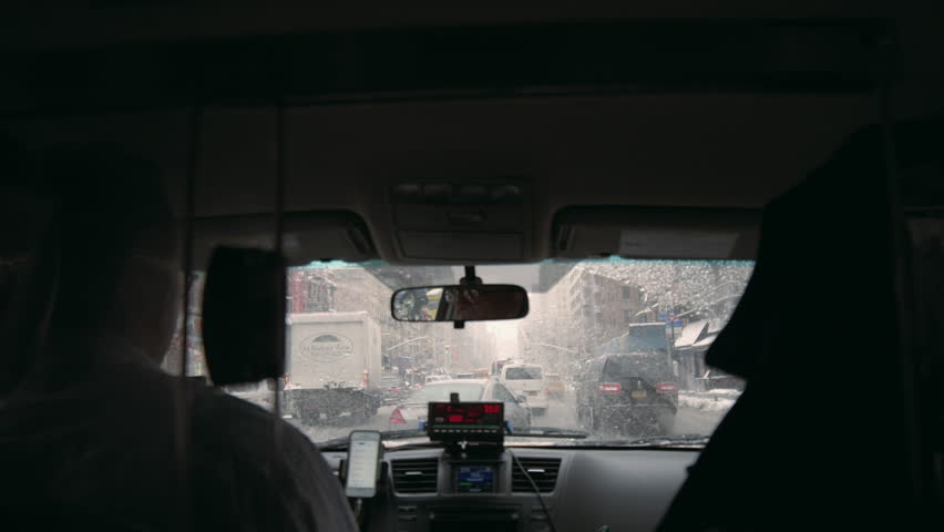 NEW YORK - MARCH 5, 2015: taxi driver interior with windshield and meter in front seat, driving in rainy street, raining in 4K Manhattan NY. Cabs can pick up passengers in the 5 boroughs of NYC.