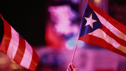 Evening shot of two Puerto Rican flags being held outdoors at an event. SInce it is a close-up, aside from the flags only the hands of the people can be seen but no faces.