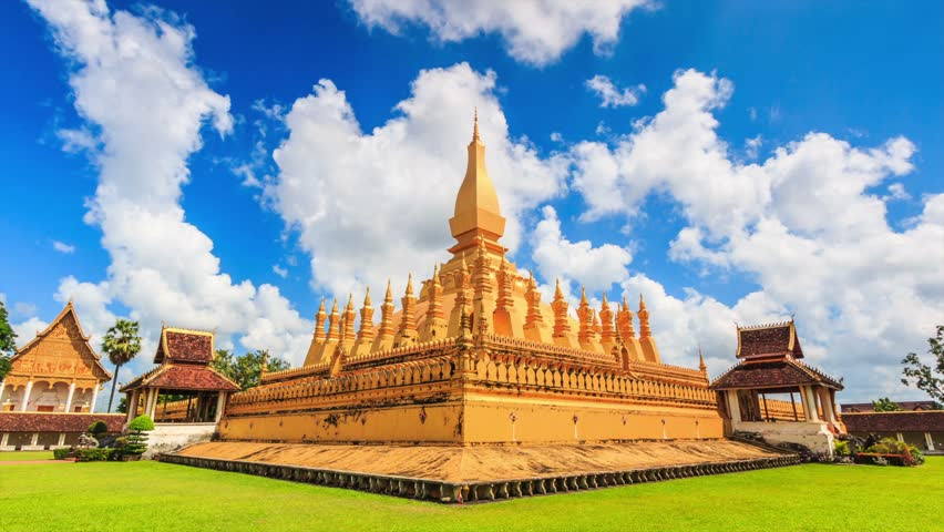 Religious Architecture And Landmarks. Golden Buddhist Pagoda Of Phra That  Luang Temple Under Blue Sky
