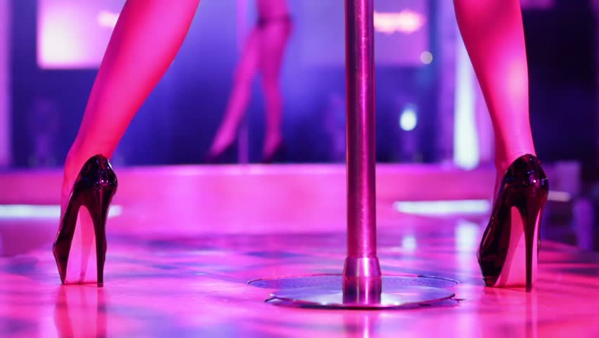 Beautiful legs of woman in high-heeled shoes dancing on a stage in a strip club.