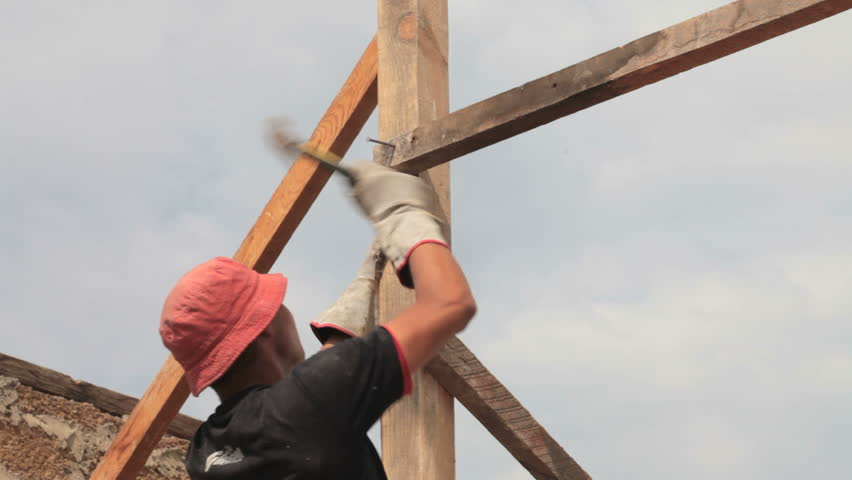 Construction roofer nailing wood board with hammer on roof installation work