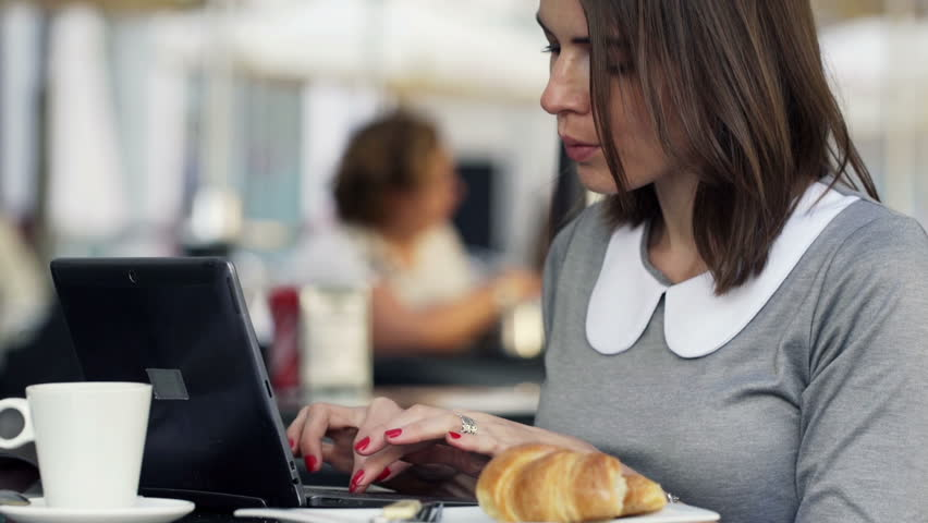 Young, attractive businesswoman working on laptop, sitting in cafe 