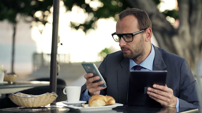 Young businessman comparing data on tablet computer and smartphone in cafe  | Shutterstock HD Video #9316211