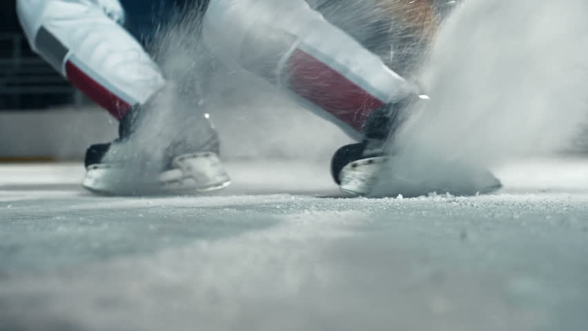 Low angle of hockey player running towards camera on skates and doing a turn cutting ice to powder | Shutterstock Video #9344261