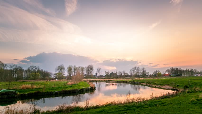 Sunset over the village of Vlodrop in the southern province of Limburg, The Netherlands. Time lapse footage with moving clouds, swans swimming in a pond.