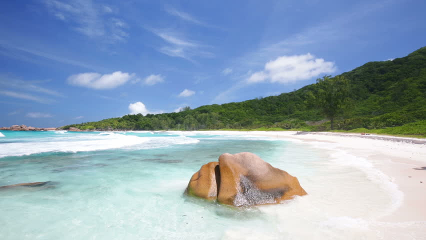 Panning shot of perfect white beach with turquoise water and granite boulders in the Seychelles. Anse Cocos, La Digue.