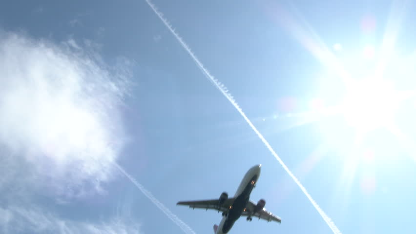 Commercial airliner flying overhead on sunny day with jet contrails lining the blue sky.