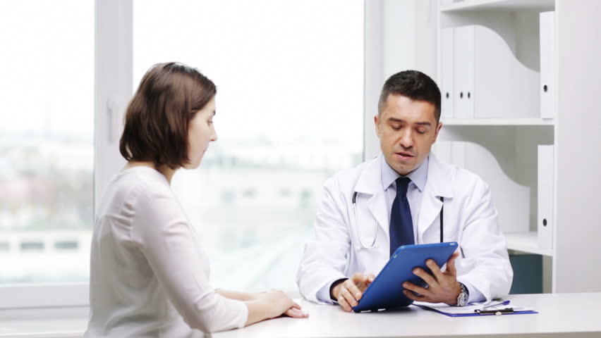 medicine, health care and people concept - smiling doctor with tablet pc computer and young woman meeting at hospital