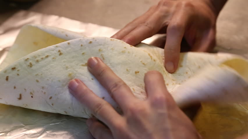 An Asian man preparing Mexican food, making delicious burritos in the kitchen of a Mexican restaurant-Dan