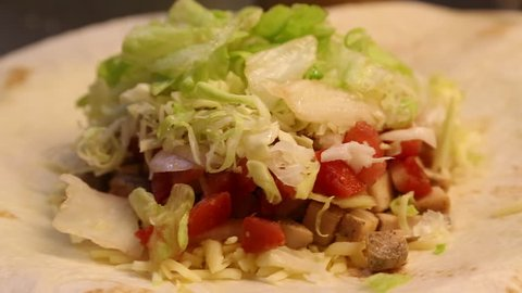 A professional chef is cooking Mexican food in restaurant, tacos and quesadillas, prepare the maize tortillas for add different ingredient, cheese, tomato, lettuce, chicken and sauce-Dan