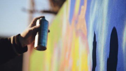Graffiti Artist Paint Spraying the Wall, Urban Outdoors Street Art Concept, Handheld 1920x1080 cinematic toned HD footage.