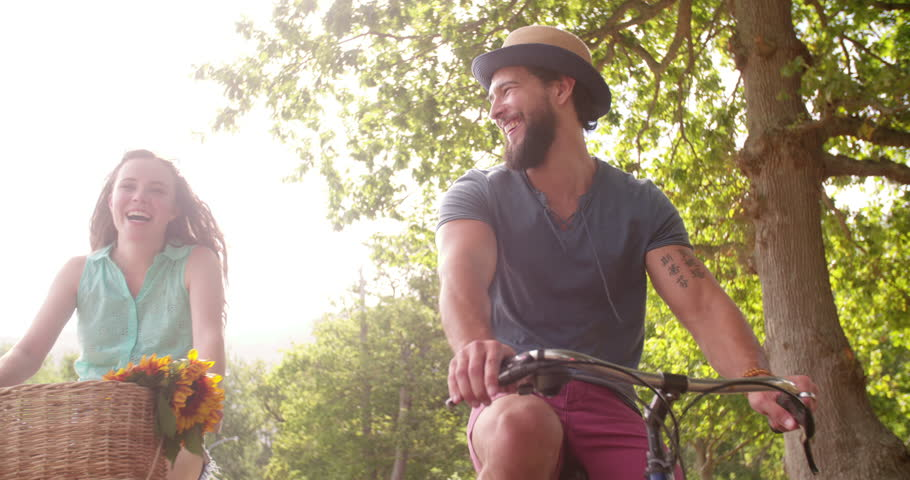 Young couple cycling happily together through a sunny park on street in summertime