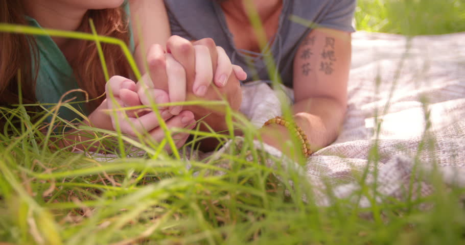 Cropped close up of affectionate couple holding hands and lying on some fresh green grass | Shutterstock HD Video #9426482