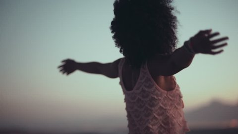 African american girl with afro haircut standing with arms wide spread enjoying the sunset