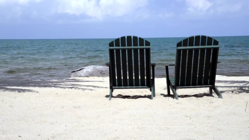 Tacking Dolly Shot Of Two Chairs On Beach Waiting For You Stock