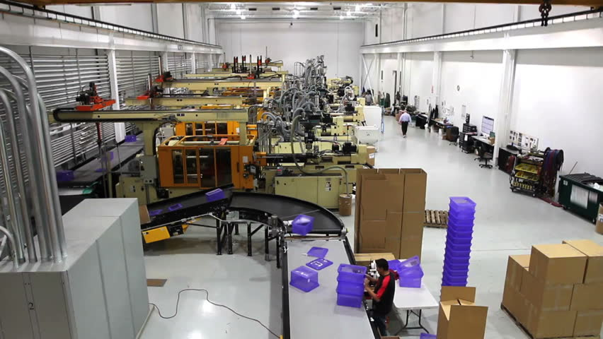 A wide shot time lapse of an entire robotics assembly plant in motion.