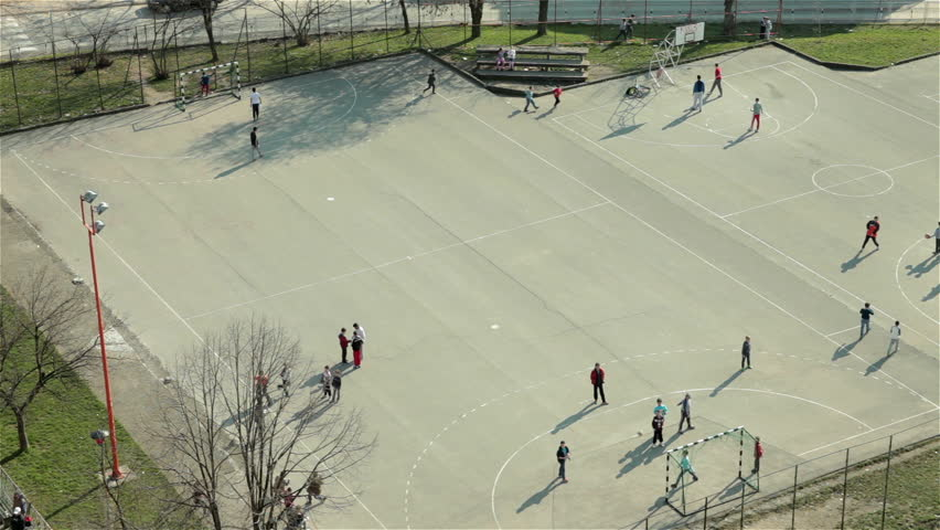 Group of children playing game with ball on school playground. Boys playing football and basketball on sport court. Kids training on school yard. Recreation,leisure time,soccer,sunny day,high angle.   Shutterstock HD Video #9442436