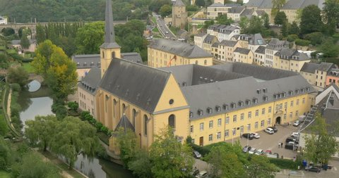 Pan tilt right camera motion of Luxembourg city, Europe, aerial view of old town architecture, medieval Neumunster abbey church in the Grund district and river Alzette, european tourism background
