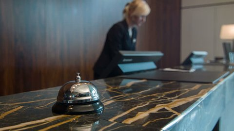 Arrival to hotel. Selective focus on smooth little bell standing on reception counter during receptionist talking to the phone on background